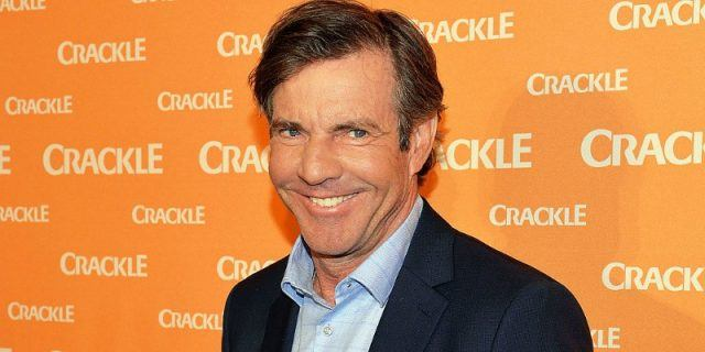 Dennis Quaid smiling in front of an orange backdrop.