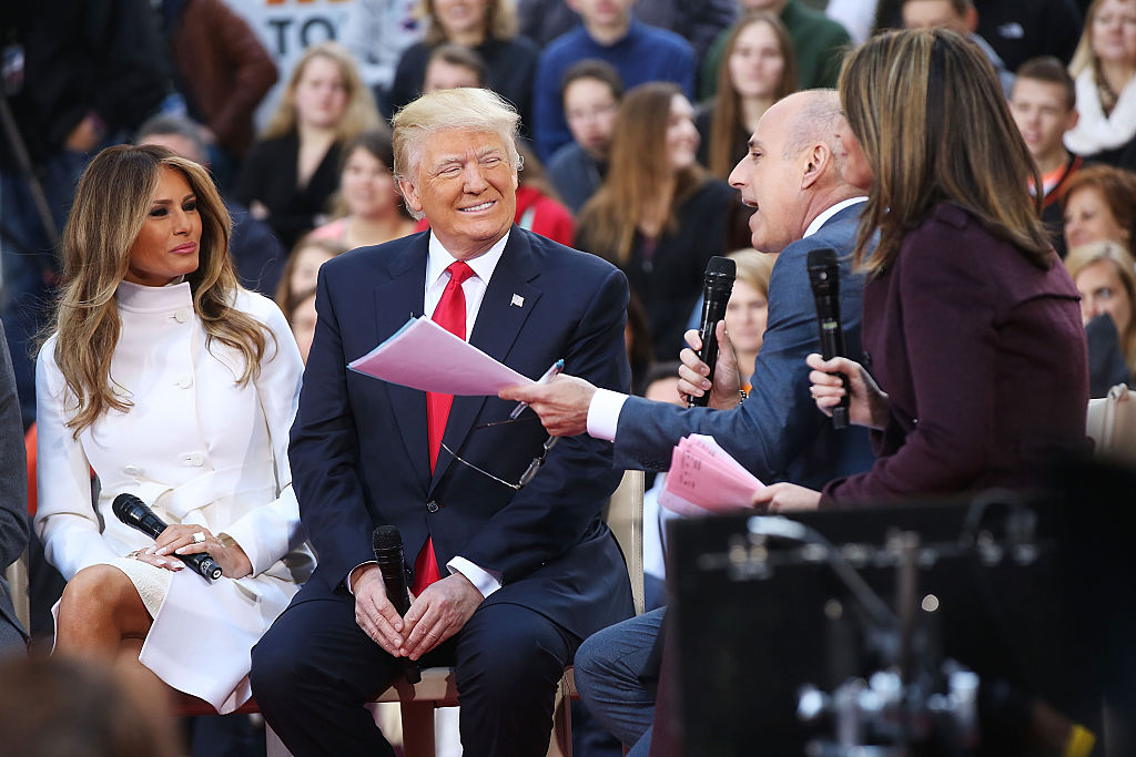 Donald Trump sits with his wife Melania Trump
