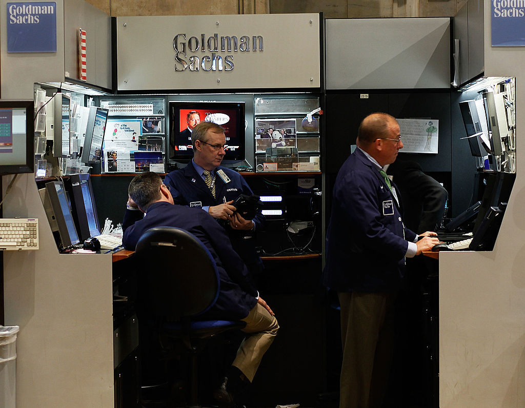 Financial professionals work in the Goldman Sachs booth on the floor of the New York Stock Exchange