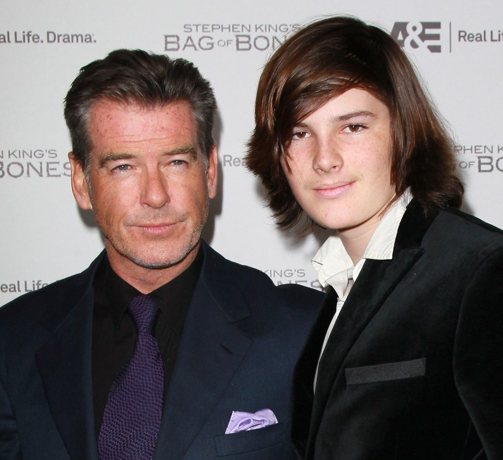Dylan and Pierce Brosnan pose together in suits on the red carpet.