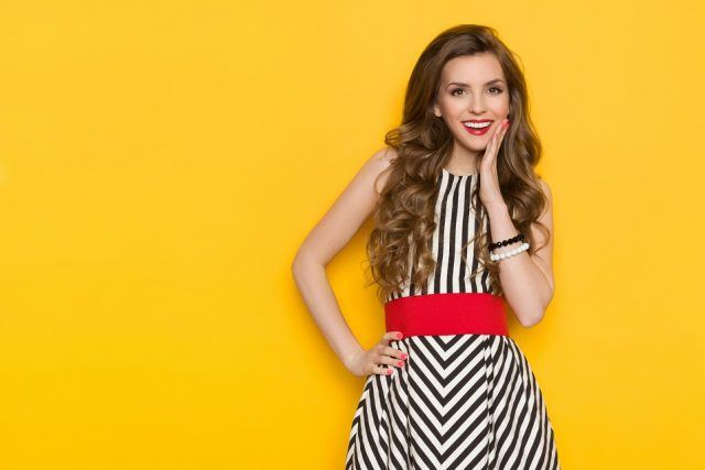 Smiling beautiful young woman in black and white striped dress