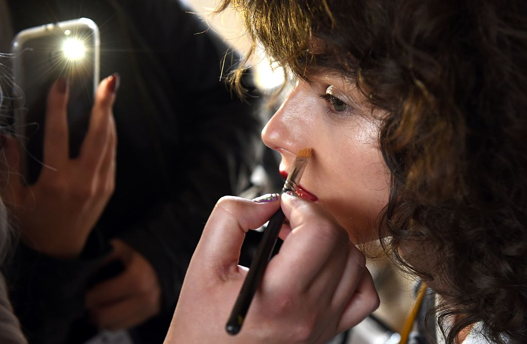 A model has her makeup attended to backstage before a showing of Australian designer