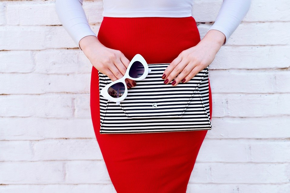 woman wearing red skirt with striped handbag clutch and sunglasses