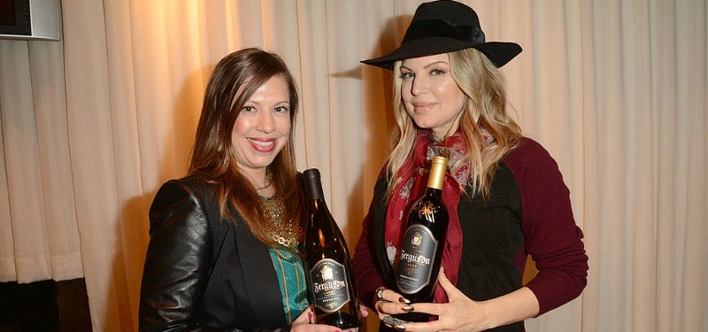 Fergie and sister Dana Ferguson posing with bottles of Ferguson Crest