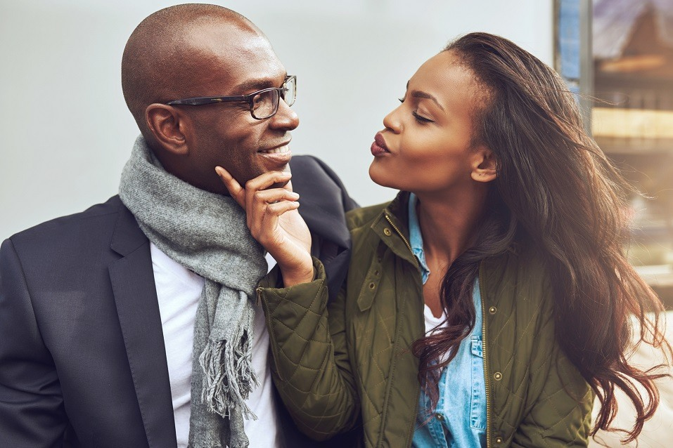A young African American woman purses her lips as she awaits a kiss from her partner