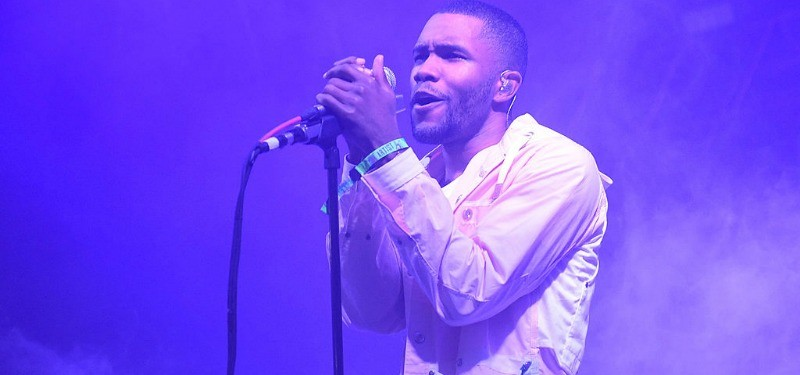 Frank Ocean is holding a microphone with both hands as he performs on stage.