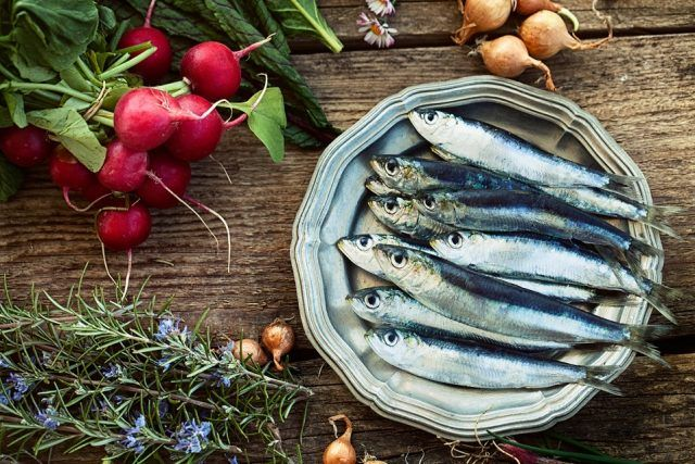Sardines and turnips on a wooden table.
