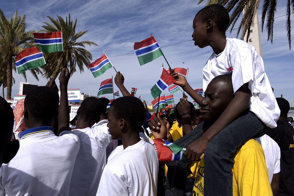 People wave Gambian flags during a protest