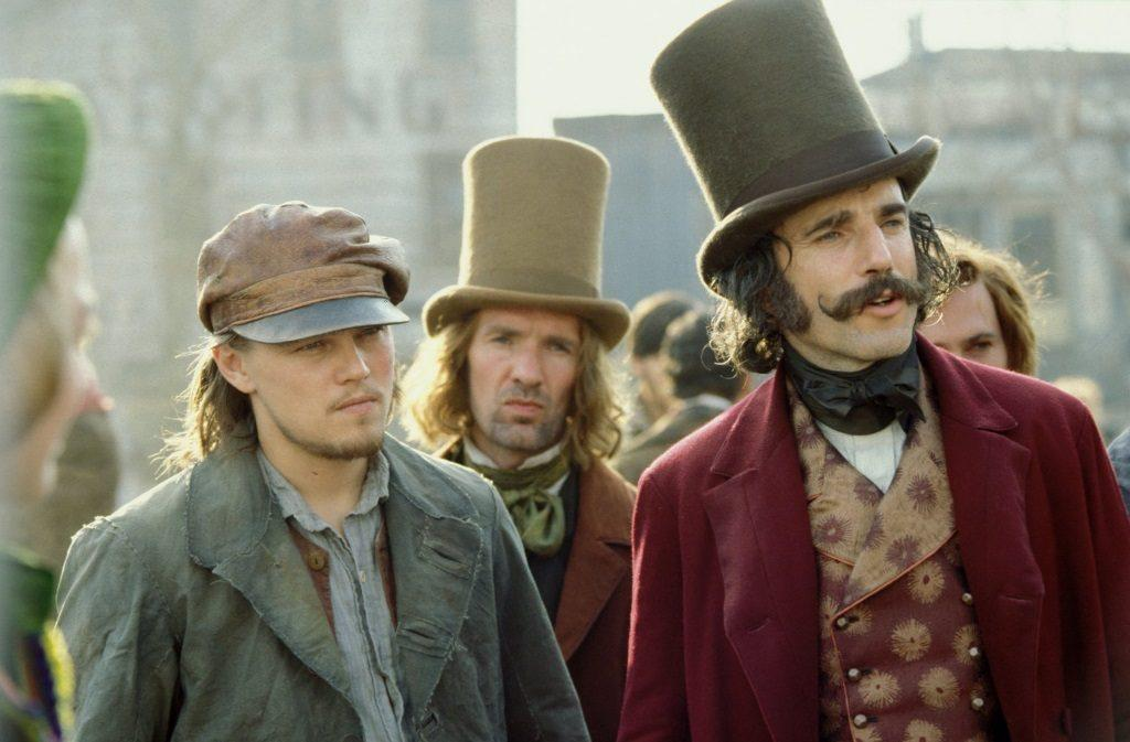 Leonardo DiCaprio and Daniel Day-Lewis stand next to each other in a crowd in Gangs of New York