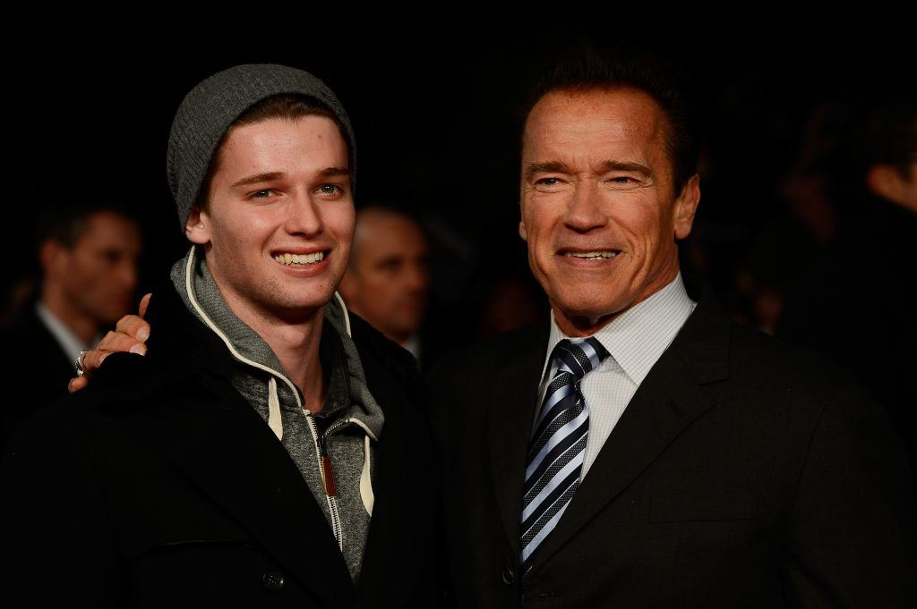 Patrick and Arnold Schwarzenegger are posing together smiling.