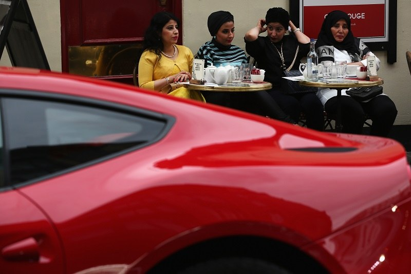 Wealthy diners eat in front of a Ferrari.