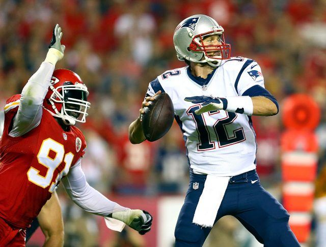 Tom Brady about to throw the foot ball