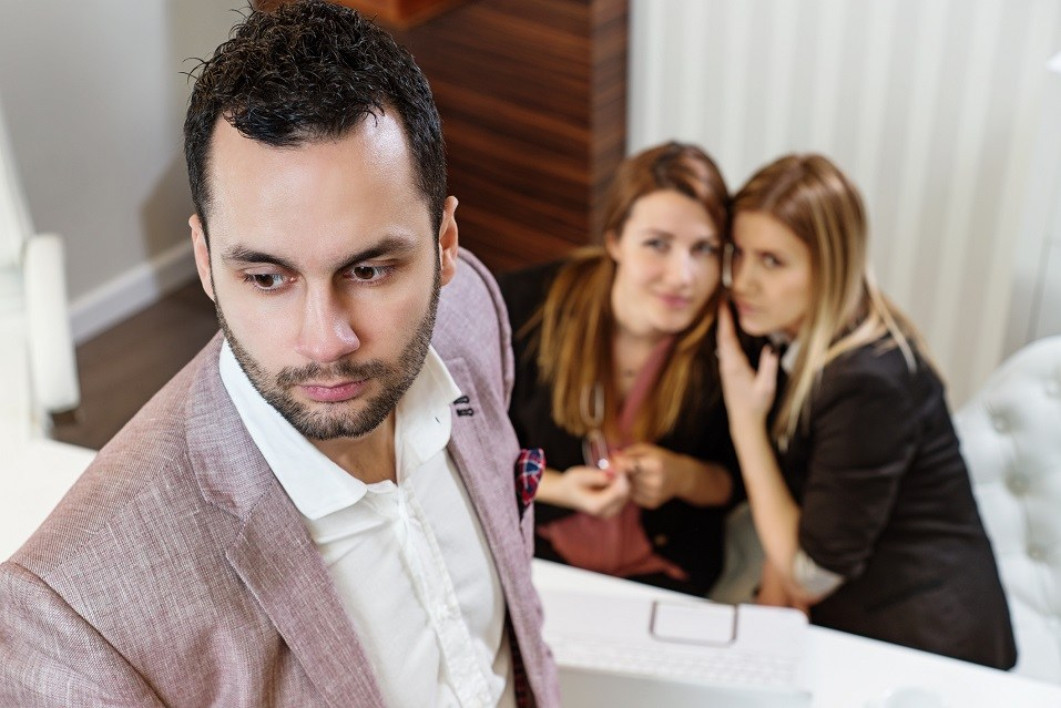 two women gossip behind man
