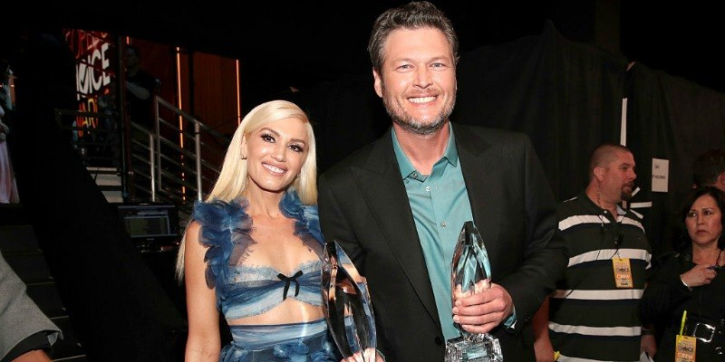 Blake Shelton and Gwen Stefani are smiling backstage at the People's Choice Awards and are holding their awards