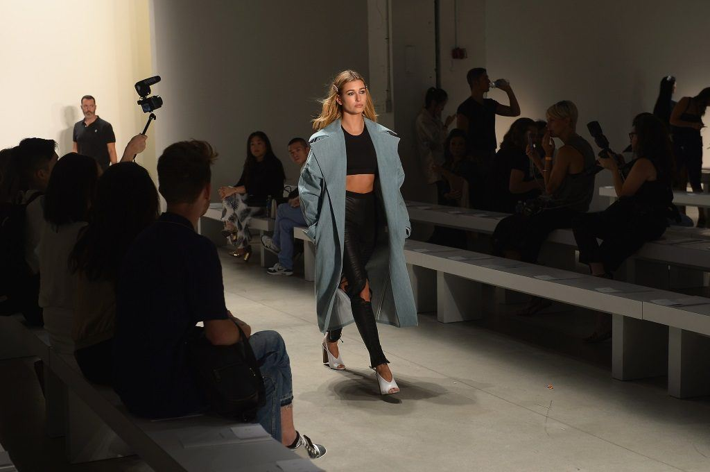 Hailey Baldwin is walking down the runway in a black outfit and a blue coat.