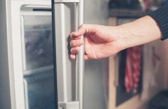 young man is opening a freezer door