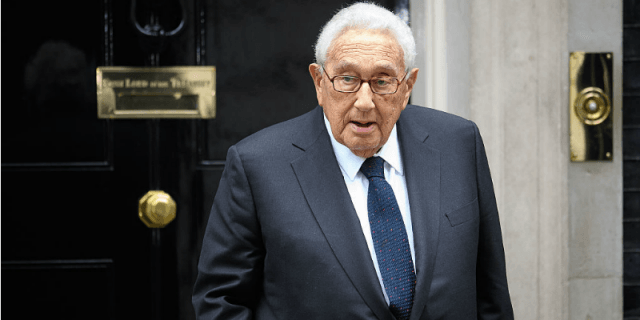 Henry Kissinger, wearing a suit, standing in front of a black door.
