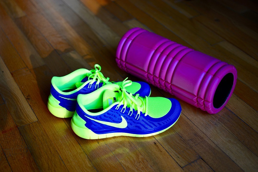 Men's Nike running shoes in green and blue and a violet foam roller