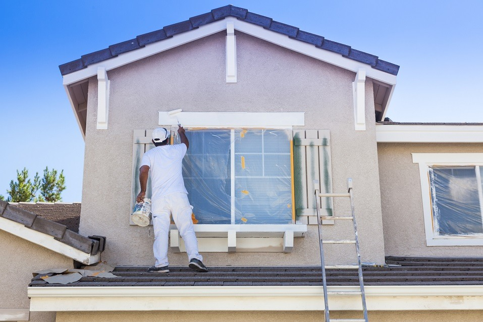 Person paints trim of house white
