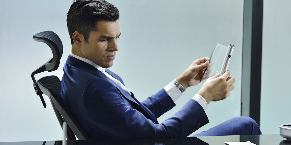 Sean Teale leans back in a desk chair while holding a gadget in SyFy's Incorporated