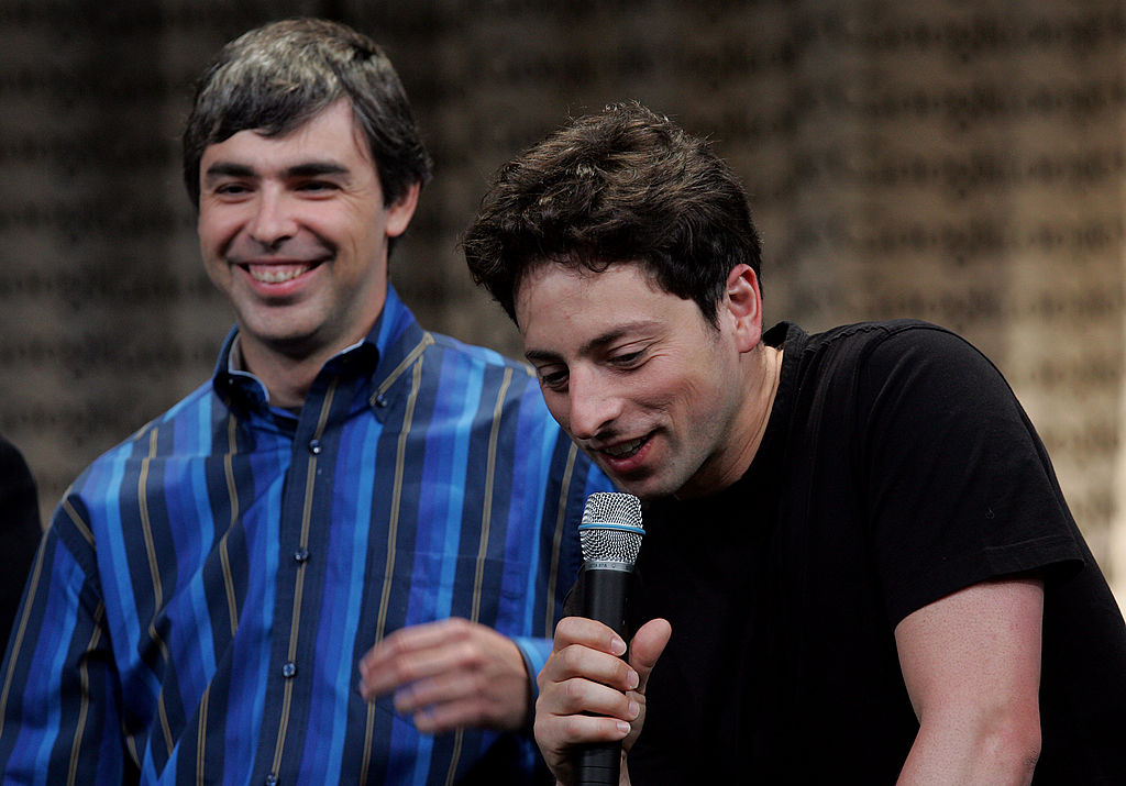 Google founders Larry Page, left, and Sergey Brin talk with members of the media