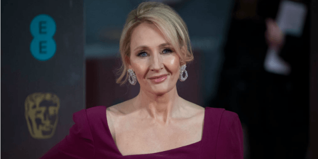J.K. Rowling in a purple dress smiling at the camera.