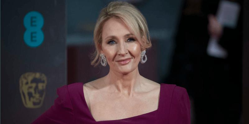 J.K. Rowling in a purple dress smirking at the camera