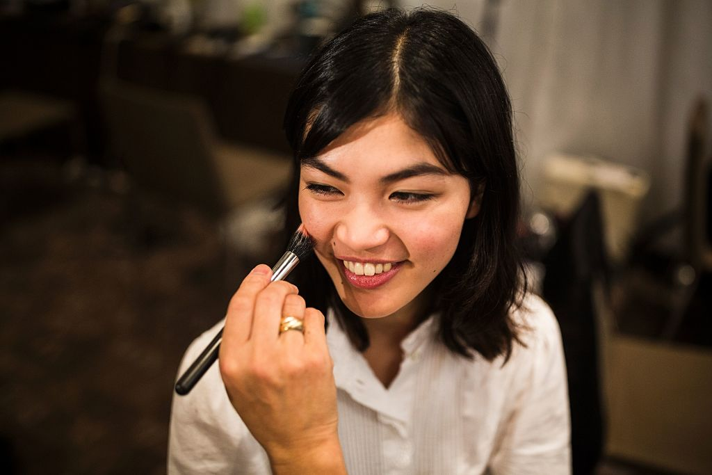a stylist works on the makeup for Japanese model Rina Fukushi