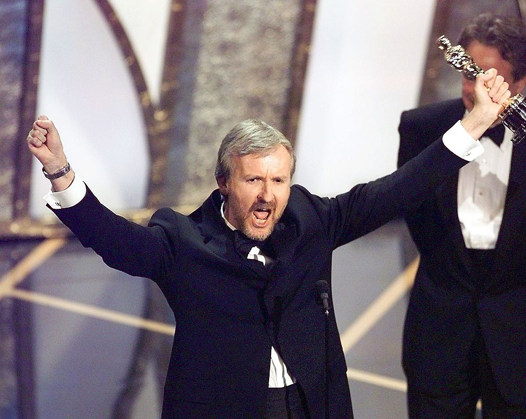 Director James Cameron raises his Oscar after winning in the Best Director Category during the 70th Academy Awards