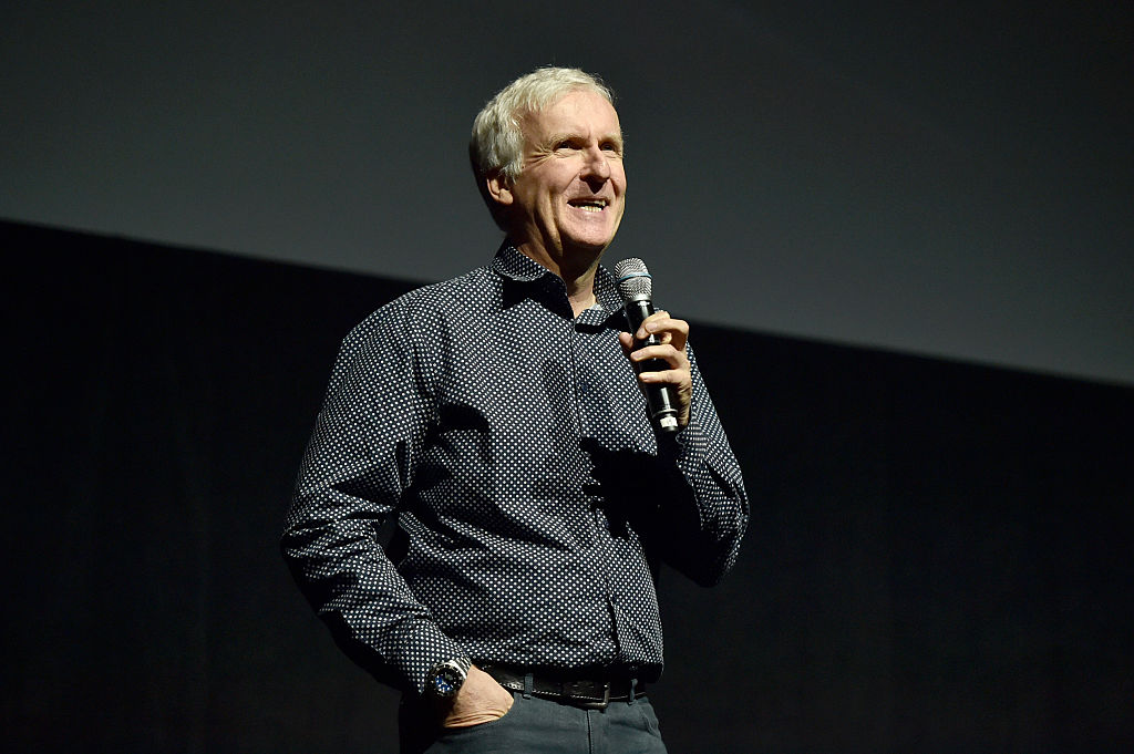 James Cameron wearing a black dress shirt, speaking into a microphone