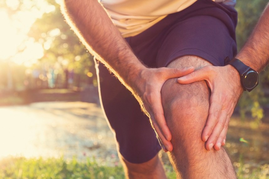 a man holding his knee from a jogging injury