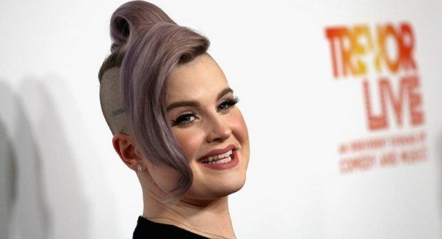 Kelly Osbourne smiling in front of a white backdrop.