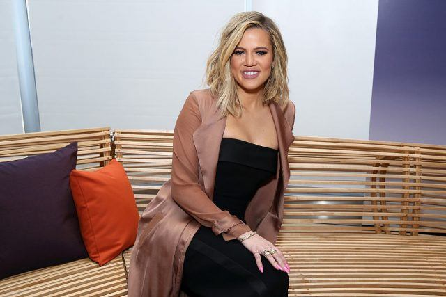 Khloe Kardashian sits on a wooden bench at a fashion show.