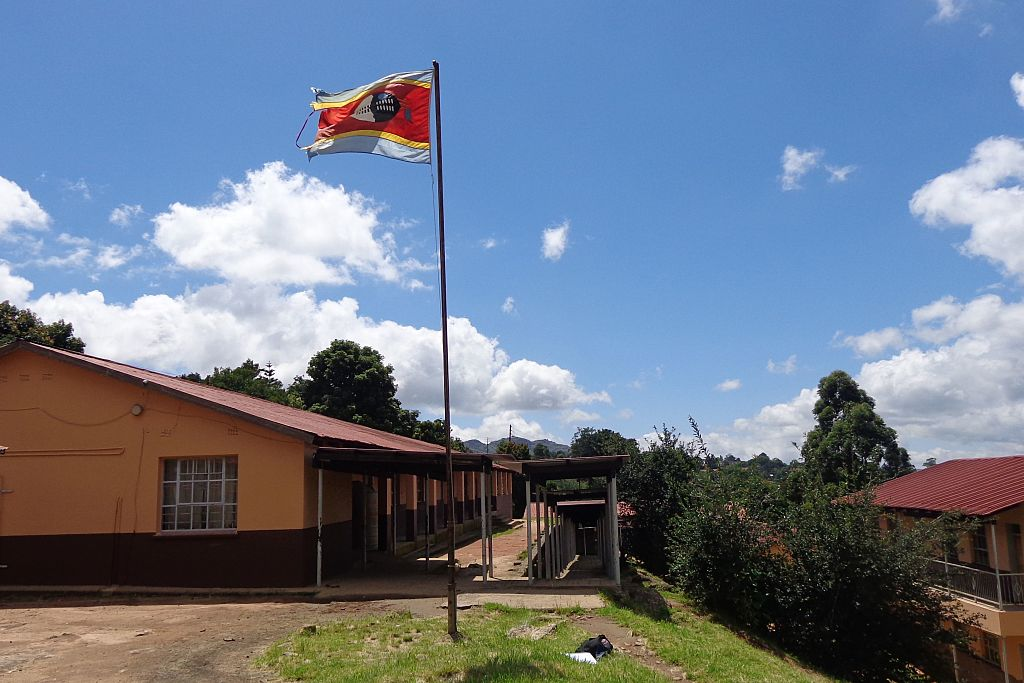 Kingdom of Swaziland flag flies on a mast by a public school