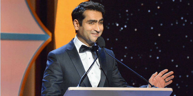 Kumail Nanjiani in a suit and at a podium