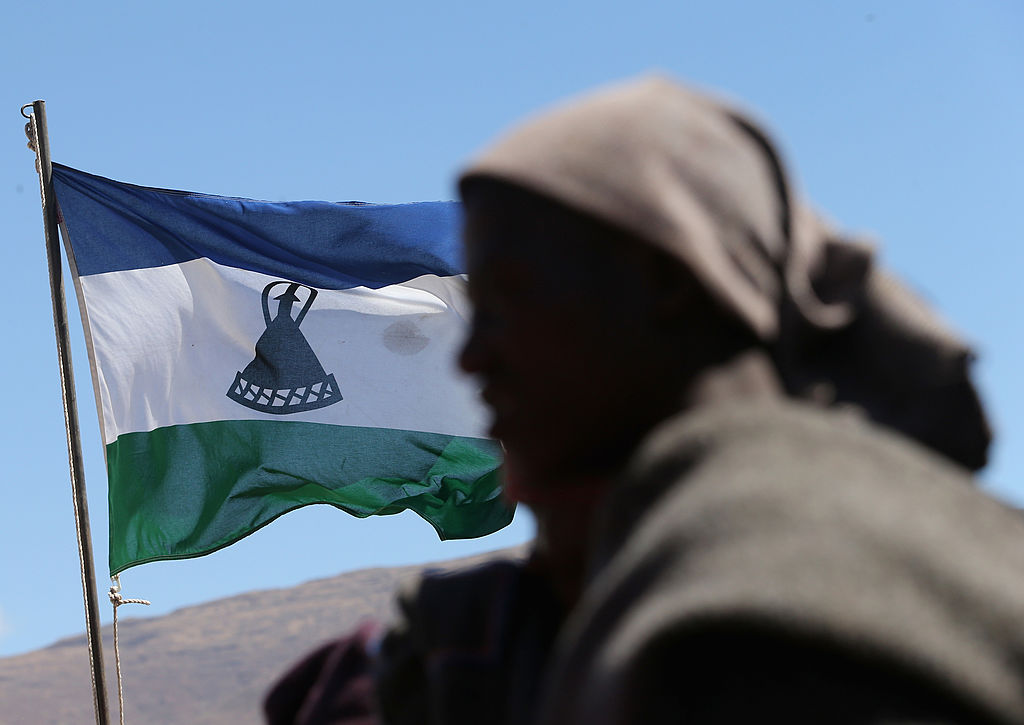 A herd boy in front of the Lesothan flag