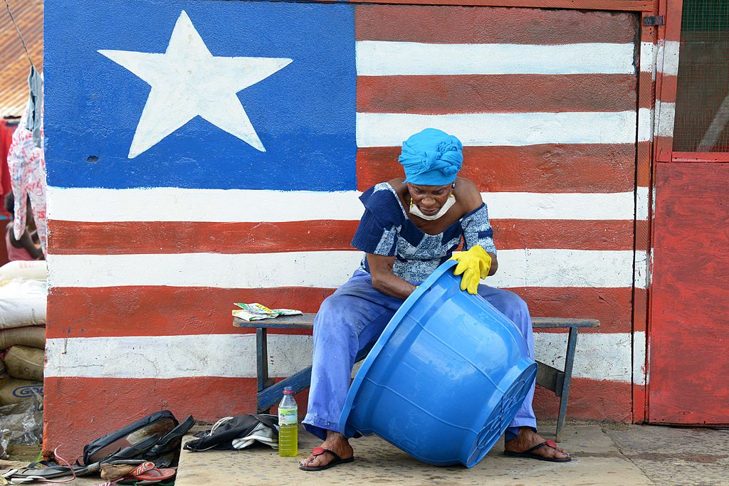 A woman sitting by a mural showing Liberia's national flag