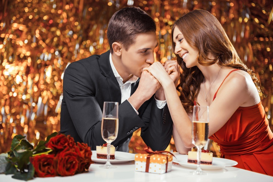 An elegantly dressed couple displays affection to one another inside a restaurant