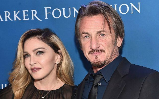 Madonna and Sean Penn posing in front of a blue backdrop.