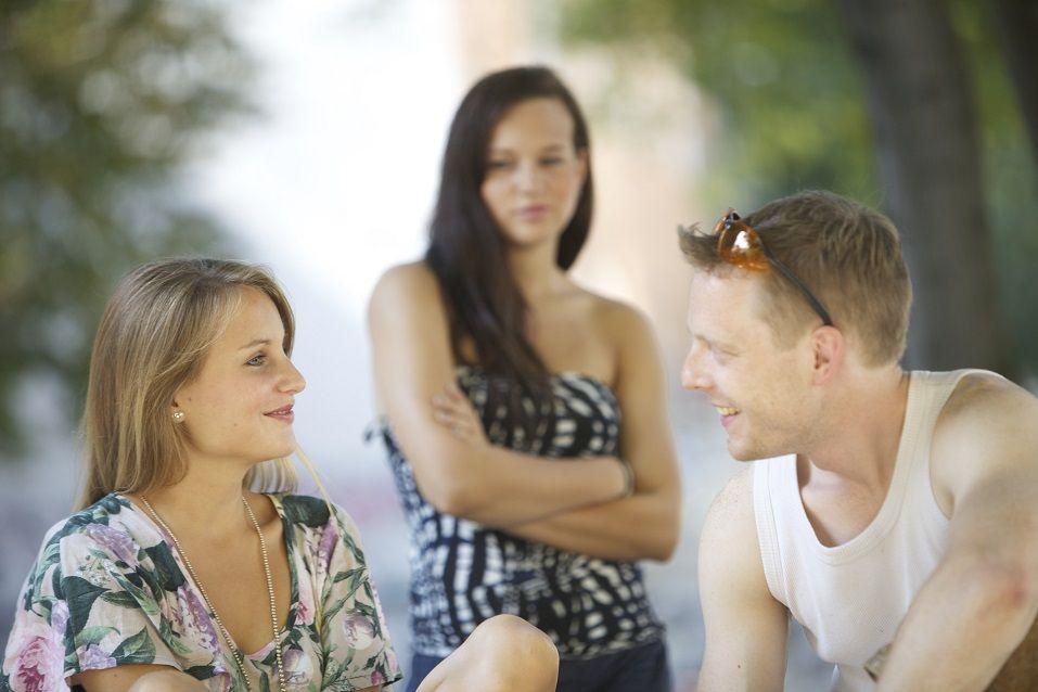 Jealous woman looks at cheerful couple