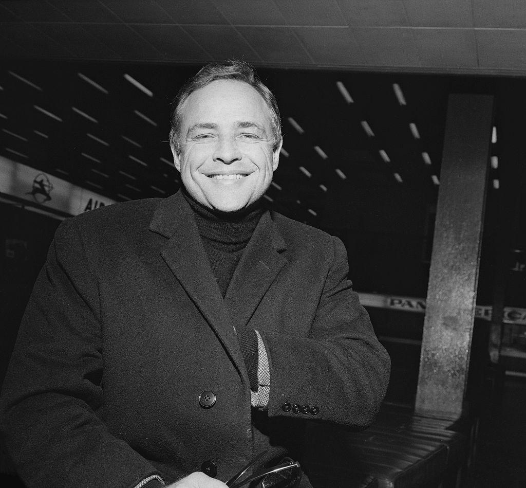 American actor Marlon Brando in an overcoat, smiling