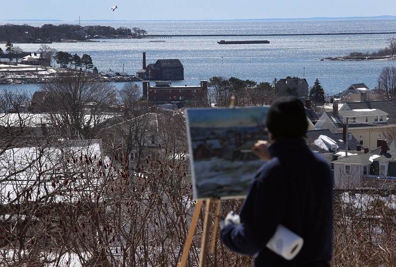 An artist paints the Gloucester Harbor in Massachusetts