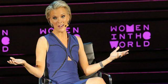 Megyn Kelly sitting on stage with both her hands out as she speaks to the audience.