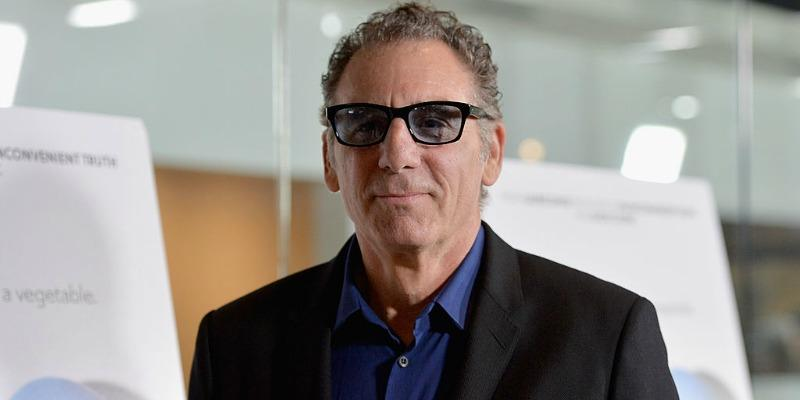 Michael Richards is in a black suit and is wearing black rimmed glasses.