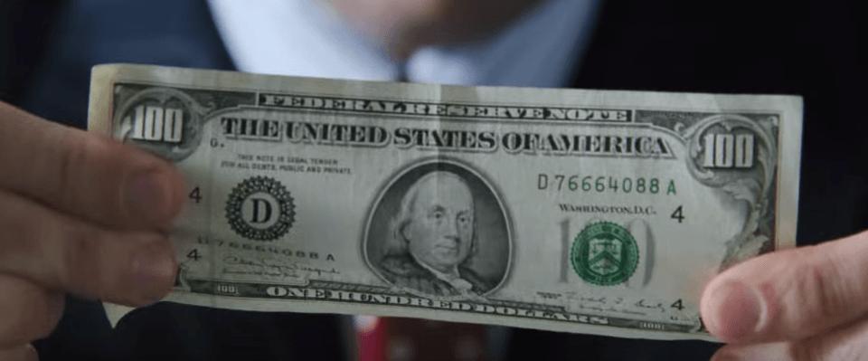 Hand holding a $100 bill