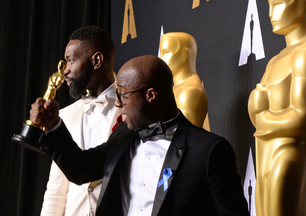 """""""Moonlight"""" director Barry Jenkins (R) and writer Tarell Alvin McCraney pose with the Oscar"""