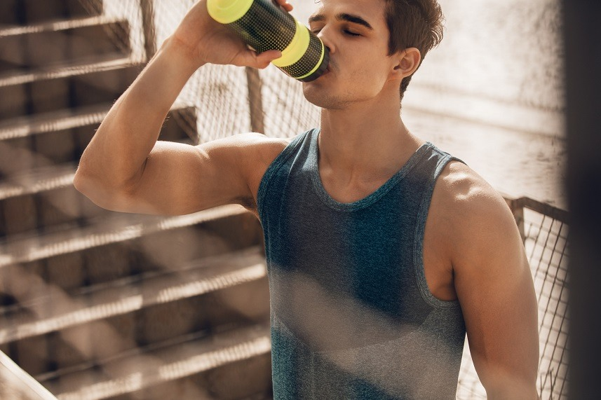 A muscular young man drinks water from a yellow water bottle