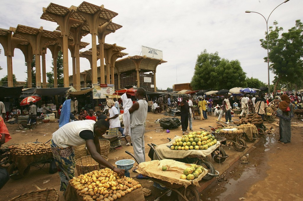 A Nigerois man rearranges his produce at the central Niamey marketplace