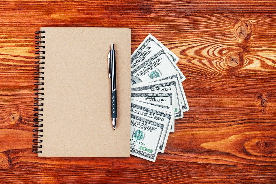 Brown notebook with dollars and pen lying on wooden table