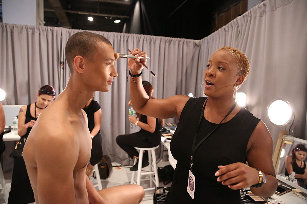 A model at hair and makeup backstage at Parke